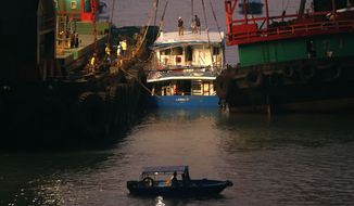 Workers on Tuesday, Oct. 2, 2012, check on a salvaged boat that sank the previous night after colliding with a ferry near Hong Kong's Lamma Island. (AP Photo/Kin Cheung)
