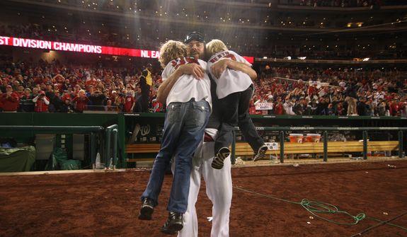 Washington Nationals right fielder Jayson Werth (28) hugs his two sons after Washington Nationals clinching National League East, sending them into the playoffs at Nationals Ballpark, Washington, D.C., Monday, Oct. 1, 2012. (Craig Bisacre/The Washington Times)