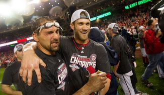 Washington Nationals left fielder Mark DeRosa (7), left, and Washington Nationals center fielder Bryce Harper (34), center, celebrate with their teammates as the Washington Nationals clinch the National League East at Nationals Park, sending them into the playoffs, Washington, D.C., Monday, October 1, 2012. (Andrew Harnik/The Washington Times)