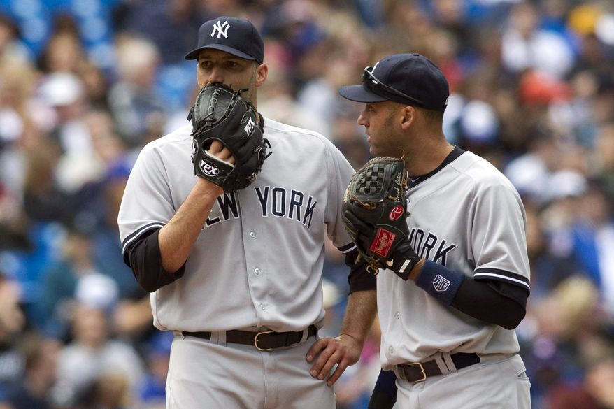 New York Yankees starting pitcher Andy Pettitte, left, confers with Derek Jeter during the sixth inning of a baseball game against the Toronto  Blue Jays in Toronto on Saturday, Sept. 29, 2012. (AP Photo/The Canadian Press, Chris Young)