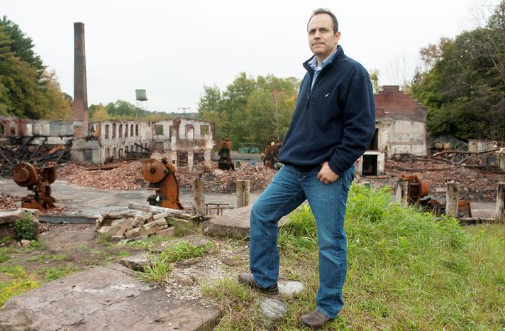 Matt Bevin, owner of 180-year-old Bevin. Bros. bell-manufacturing company in East Hampton, Conn., stands by the remains of his burned-out factory. Production has resumed in a rented warehouse, and a new factory will be built. (Associated Press)