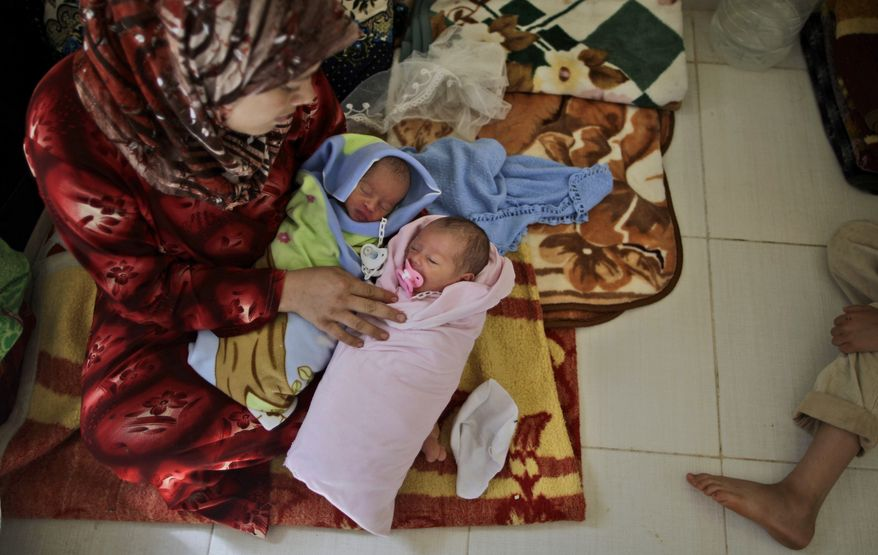 **FILE** Fatimah Abdullah, 29, sits Sept. 7, 2012, next to her 4-day-old twins, Ahmad and Bayan, who were born in a Turkish hospital, near the Syrian town of Azaz. Abdullah, who fled her home in Marea, Syria, 15 days before due to Syrian government shelling, took her children to the Bab Al-Salameh border crossing in hopes of entering one of the refugee camps in Turkey. (Associated Press)