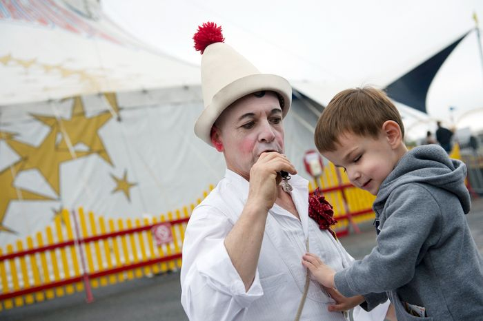 """Matthew Dovi, 4, of McLean, Va., who is blind, feels the chest of Pinot the clown, aka Mark Jaster, as he blows a whistle outside the Big Apple Circus tent before a special """"Circus of the Senses"""" performance on Wednesday, Oct. 3, 2012 in Sterling, Va.  (Barbara L. Salisbury/The Washington Times)"""