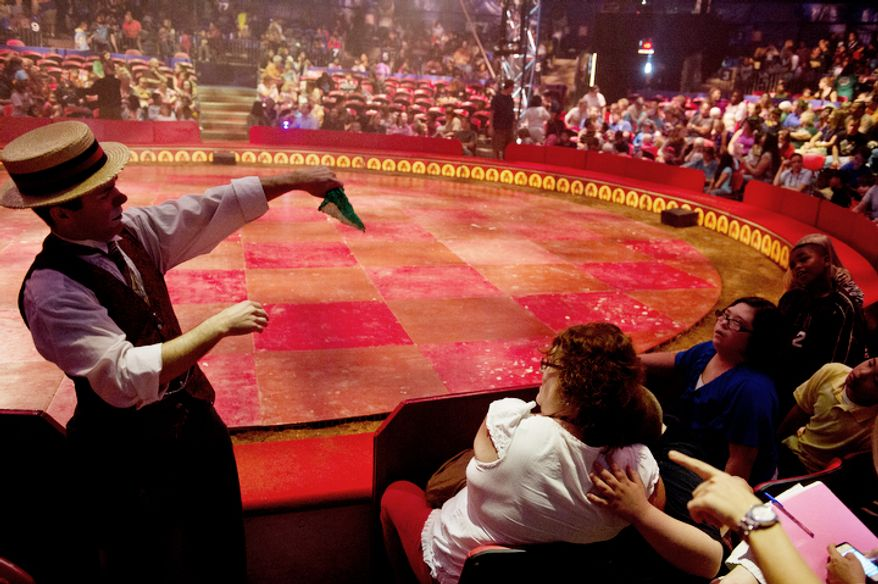 """Matthew Pauli, left, aka Dr. Spats the clown, performs in the audience before the start of the Big Apple Circus's """"Circus of the Senses"""" performance. The free performance was designed for children with sensory impairments and more than 1,200 people attended. (Barbara L. Salisbury/The Washington Times)"""