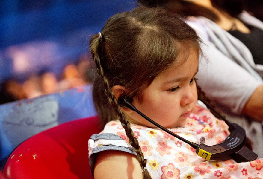 "Five-year-old Maria Zoerlein, of Alexandria, Va., who is visually impaired, uses a special wireless headset to listen to live audio description of the Big Apple Circus's special ""Circus of the Senses"" performance.  (Barbara L. Salisbury/The Washington Times)"