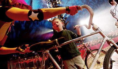 """Max Smith-Levin, 7, of Warrenton, Va., feels one of the bicycles from the Dalian Acrobatic Troupe during a special """"touch session"""" following the Big Apple Circus's """"Circus of the Senses"""" performance on Wednesday, Oct. 3, 2012 in Sterling, Va. Max is one of the visually impaired audience members who was invited into the ring after the show to get an up-close look at some of the props and costumes. (Barbara L. Salisbury/The Washington Times)"""