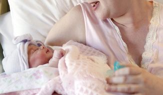 A mother holds her newborn baby at Christus Spohn Hospital South in Corpus Christi, Texas, on Friday, Nov. 11, 2011. (AP Photo/Corpus Christi Caller-Times, Michael Zamora)
