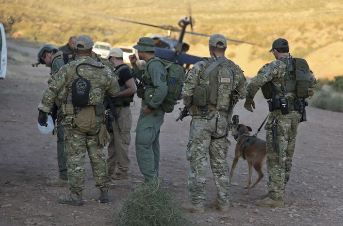 **FILE** Law enforcement officers gather Oct. 2, 2012, at a command post in the desert near Naco, Ariz., after a Border Patrol agent was shot to death near the U.S.-Mexico line. The agent, Nicholas Ivie, 30, and a colleague were on patrol about 100 miles from Tucson, when shooting broke out shortly before 2 a.m., the Border Patrol said. (Associated Press/U.S. Customs and Border Protection)