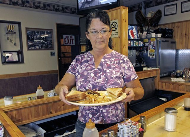 **FILE** Millie Brown, a cook and waitress at Buch's Truck Stop in Steubenville, Ohio, serves a breakfast Sept. 27, 2012. (Associated Press)