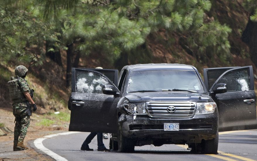 Military personnel check an armored U.S. Embassy vehicle after it was attacked by unknown assailants on the highway to Cuernavaca, Mexico, on Friday, Aug. 24, 2012, near Tres Marias. (AP Photo/Alexandre Meneghini)