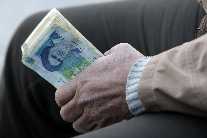 **FILE** An Iranian street money changer holds Iranian banknotes with a portrait of late revolutionary founder Ayatollah Khomeini in the main old Bazaar of Tehran. (Associated Press)