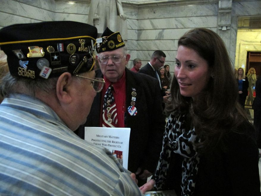 Kentucky Secretary of State Alison Lundergan Grimes, right, speaks with veterans on Wednesday, Sept. 19, 2012, at the Capitol in Frankfort, Ky. Grimes is pressing for legislation to make it easier for deployed troops to vote in Kentucky elections. (AP Photo/Roger Alford)