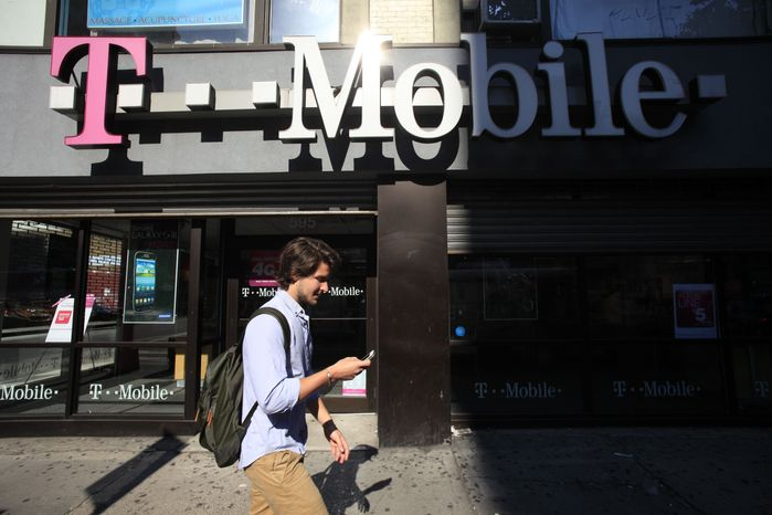A cellphone-using pedestrian passes a T-Mobile store on Wednesday, Sept. 12, 2012, in New York. (AP Photo/Mark Lennihan)