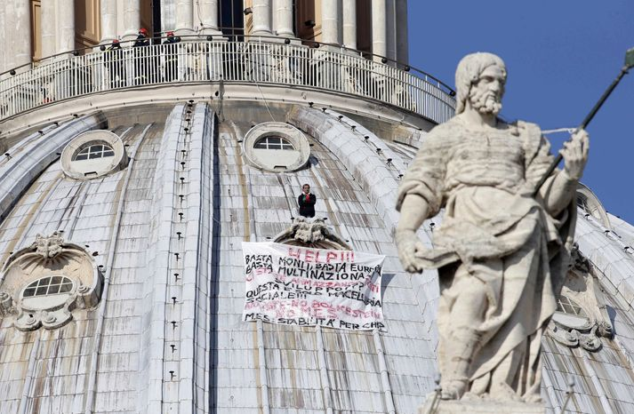 Firefighters look down at Italian businessman Marcello di Finizio, who is protesting economic cutbacks in Italy by climbing up the dome of St. Peter's Basilica at the Vatican on Wednesday, Oct. 3, 2012. (AP Photo/Andrew Medichini)