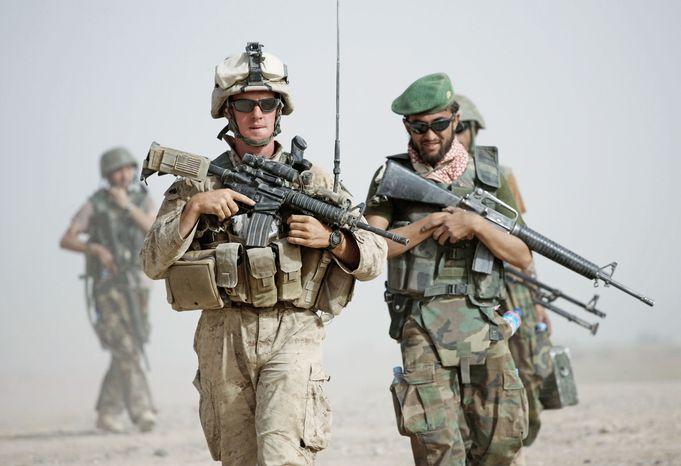 ** FILE ** A U.S. Marine squad leader patrols alongside an Afghan National Army lieutenant in Helmand province in Afghanistan. (Associated Press)