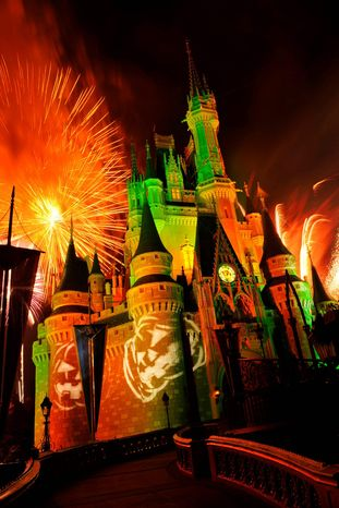 "Fireworks explode over Cinderella's Castle while illuminated pumpkins are projected with light during the ""Happy HalloWishes"" fireworks show at Walt Disney World's Magic Kingdom in Lake Buena Vista, Fla. (AP Photo/Disney, Gene Duncan)"