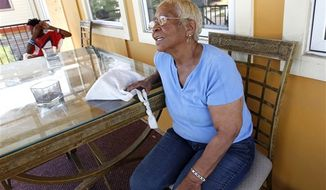 Lower 9th Ward resident Gloria Guy talks on her front porch in New Orleans, Tuesday, Oct. 2, 2012. Residents and the City of New Orleans may be pushing back against tour companies ushering out-of-towners into to the Lower 9th Ward, the neighborhood made famous when floodwalls and levees failed in 2005, pushing homes off their foundations and stranding residents on rooftops. (AP Photo/Gerald Herbert)