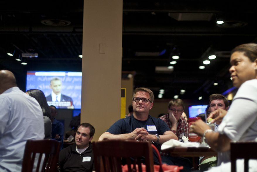 Greg Guice, of Arlington, Va., watches the first presidential debate between President Obama and Republican nominee Mitt Romney during a watch party put on by the Arlington Young Democrats and the Arlington County Democratic Committee at Bailey's Pub in Ballston Common Mall, Ballston, Va., Wednesday, Oct. 3, 2012. (Craig Bisacre/The Washington Times)