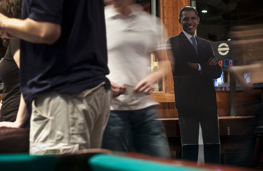 A life-size cutout of President Obama stands on the side of the sign-in table at a watch party put on by the Arlington Young Democrats and the Arlington County Democratic Committee at Bailey's Pub in Ballston Common Mall, Ballston, Va., Wednesday, Oct. 3, 2012. (Craig Bisacre/The Washington Times)