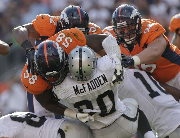 Oakland Raiders running back Darren McFadden (20) is stopped by Denver Broncos outside linebacker Von Miller (58), defensive end Mitch Unrein (96) and outside linebacker Wesley Woodyard (52) during the third quarter of an NFL football game, Sunday, Sept. 30, 2012, in Denver. (AP Photo/Joe Mahoney)