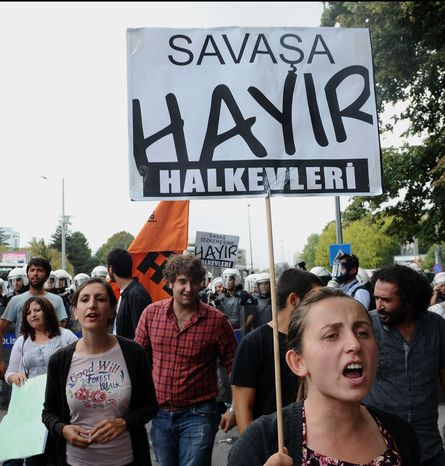 """Protesters hold banners that read """"No to War"""" during a debate at Turkey's parliament in Ankara, Turkey, on Oct. 4, 2012, after Turkey fired on Syrian targets for a second straight day. Turkey said it has no intention of declaring war, despite rising tensions after deadly shelling from Syria killed five civilians in a Turkish border town. (Associated Press)"""
