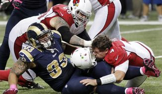 Arizona Cardinals quarterback Kevin Kolb (bottom right) is sacked by St. Louis Rams defensive tackle Jermelle Cudjo (bottom left) as Cardinals' Adam Snyder gets in on the play during the third quarter of the Rams' 17-3 home win on Oct. 4, 2012. (Associated Press)
