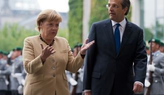 **FILE** German Chancellor Angela Merkel (left) talks Aug. 24 2012, to Prime Minister of Greece Antonis Samaras during a welcome ceremony at the chancellery in Berlin. (Associated Press/dapd/Maja Hitij)