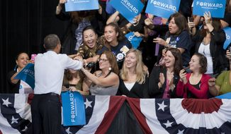 President Obama greets supporters on stage during a campaign event Friday, Oct. 5, 2012, at George Mason University in Fairfax, Va. (Craig Bisacre/The Washington Times)
