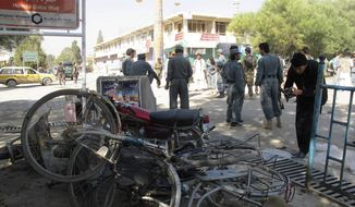 Afghan police secure the site of a suicide bombing in Khost, south of Kabul, Afghanistan, Monday, Oct. 1, 2012. The suicide bomber was driving a motorcycle packed with explosives and rammed it into a patrol of Afghan and international forces, killing over a dozen people, including three NATO service members and their translator, official said. (AP Photo/Nashanuddin Khan)