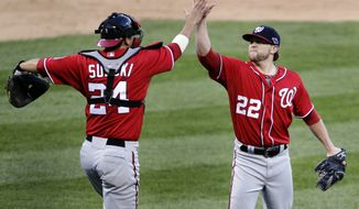 Washington Nationals relief pitcher Drew Storen, right, and catcher Kurt Suzuki celebrate theirs 3-2 win over the St. Louis Cardinals in Game 1 of baseball's National League division series, Sunday, Oct. 7, 2012, in St. Louis. (AP Photo/Tom Gannam)