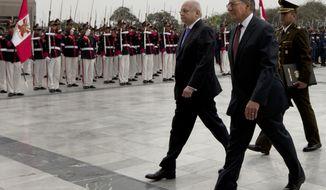 U.S. Defense Secretary Leon E. Panetta (center) walks with Peruvian Defense Minister Pedro Cateriano (left) past an honor guard during a ceremony at army headquarters in Lima, Peru, on Saturday, Oct. 6, 2012. (AP Photo/Martin Mejia)