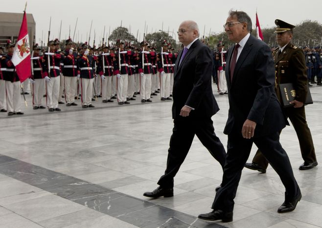 U.S. Defense Secretary Leon E. Panetta (center) walks with Peruvian Defense Minister Pedro Cateriano (left) past an honor guard during a ceremony at army headquarters in Lima, Peru, on Saturday, Oct. 6, 2012. (AP Photo/Martin Mejia)