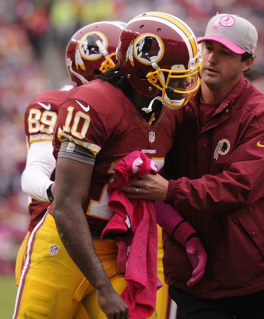 With the trainer assisting him, Washington Redskins quarterback Robert Griffin III (10) staggers off the field after being hit in the third quarter at FedEx Field, Landover, Md., Oct. 10, 2012. (Preston Keres/Special to The Washington Times)