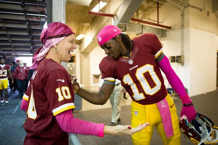 Washington Redskins quarterback Robert Griffin III (10) gives an autograph to Karen Ribiro [cq] of Fairfax, Va., who is undergoing chemotherapy as the NFL recognizes breast cancer awareness month before the Washington Redskins play the Atlanta Falcons at FedEx Field, Landover, Md., Sunday, October 7, 2012. (Andrew Harnik/The Washington Times)