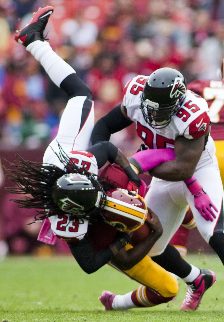 Washington Redskins quarterback Robert Griffin III (10) is sacked in the first quarter by Atlanta Falcons cornerback Dunta Robinson (23) , Landover, Md., Sunday, Oct. 7, 2012.  (Craig Bisacre/The Washington Times)