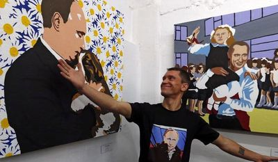 "Artist Alexei Sergiyenko shows off his paintings of Russian President Vladimir Putin during the opening of the exhibition ""Putin: The Most Kind-Hearted Man in the World"" at the Flacon design workshop in Moscow on Sunday Oct. 7, 2012. (AP Photo/Sergey Ponomarev)"