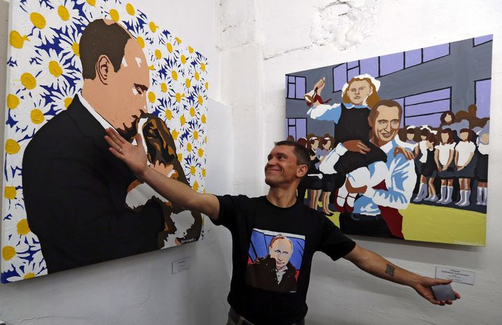"""Artist Alexei Sergiyenko shows off his paintings of Russian President Vladimir Putin during the opening of the exhibition """"Putin: The Most Kind-Hearted Man in the World"""" at the Flacon design workshop in Moscow on Sunday Oct. 7, 2012. (AP Photo/Sergey Ponomarev)"""
