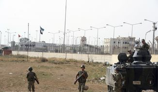 The Turkish military guards the border with Syria at a station in Akcakale, Turkey, across from Syrian-rebel-controlled Tel Abyad town (right), on Sunday, Oct. 7, 2012. (AP Photo)