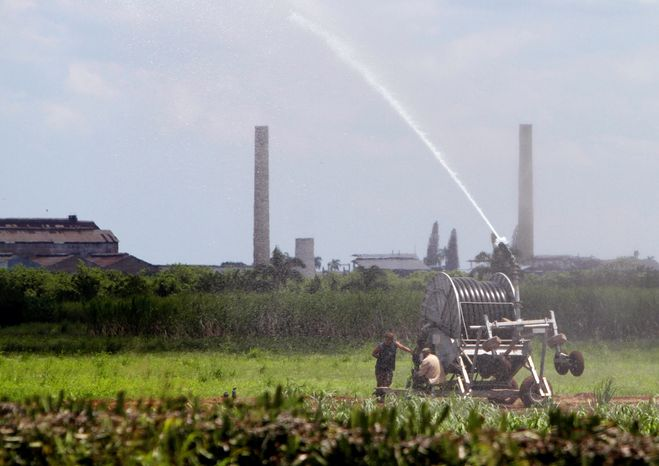Workers irrigate a sugar cane field in Jaronu, Cuba. Two years ago, the sugar industry was crippled after the worst harvest in more than a century. (Associated Press)