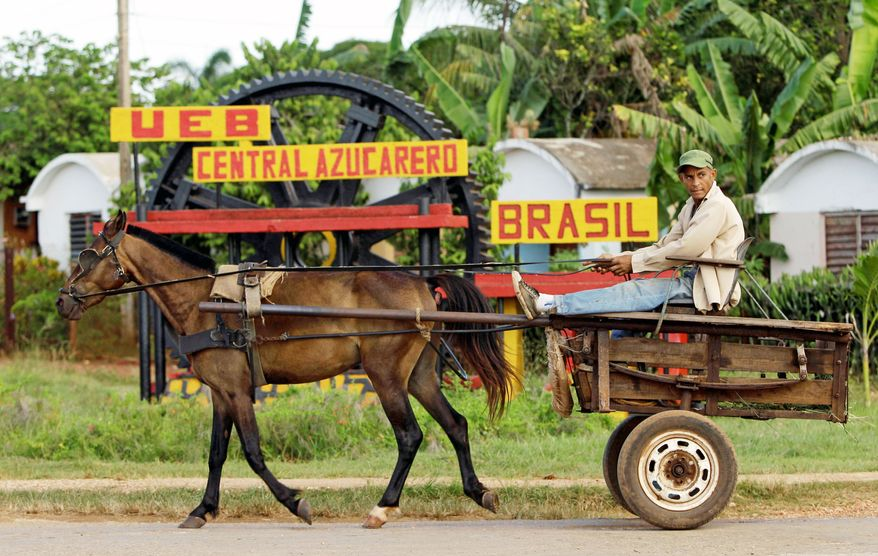 A rider in a horse-drawn carriage passes outside the Brasil sugar processing plant in Jaronu, Cuba, where a worker walks among old machinery. (Associated Press)