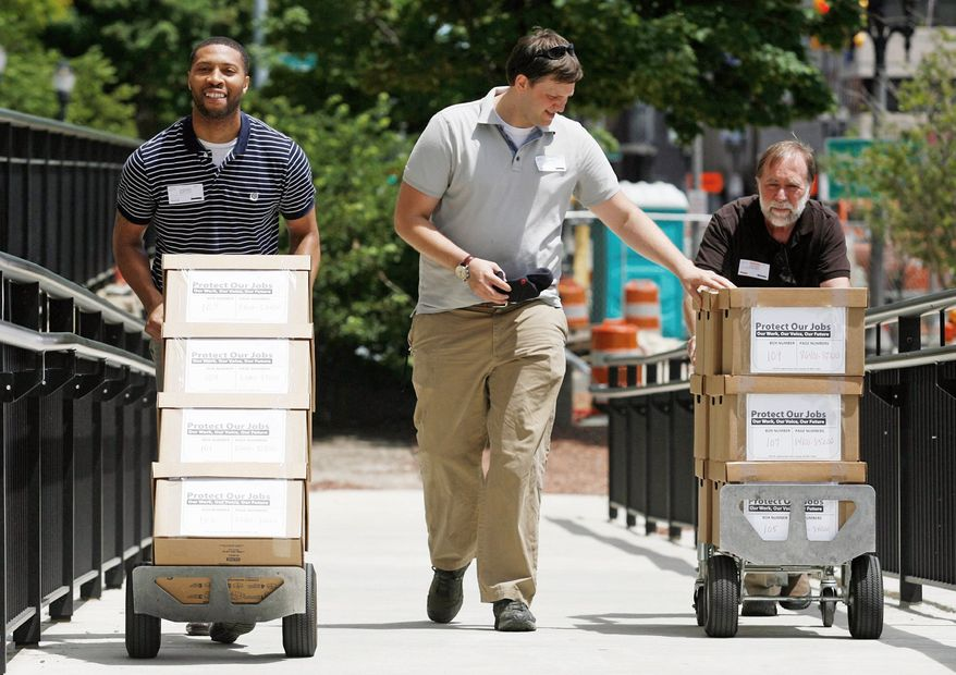 Associated press photographs Micheal Davis, left, Eric Keller, center, and Douglas Norton, right, volunteers with the Protect Our Jobs Coalition, deliver boxes of petitions for a proposal to add collective bargaining rights for workers into the Michigan Constitution to the state Bureau of Elections Wednesday, June 13, 2012, in Lansing, Mich. The Protect Our Jobs initiative was launched in March. It pushes back against a possible right-to-work movement in Michigan, which seeks to ban labor contracts that mandate payments to unions. (AP Photo/Al Goldis)