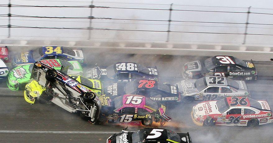 Tony Stewart (14) flips over as Kasey Kahne (5), Clint Bowyer (15), Dave Blaney (36), Terry Labonte (32), Regan Smith (78), Jeff Burton (31), Jimmie Johnson (48), Dale Earnhardt Jr. (88), Paul Menard (27) and David Ragan (34) crash around him during the NASCAR Sprint Cup Series auto race at Talladega Superspeedway in Talladega, Ala., Sunday, Oct. 7, 2012. (AP Photo/Dale Davis)