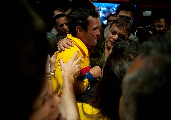 Opposition presidential candidate Henrique Capriles is greeted by supporters after he conceded defeat in the presidential elections at his campaign headquarters in Caracas, Venezuela, on Sunday, Oct. 7, 2012.  Venezuela's electoral council said late Sunday that President Hugo Chavez had won re-election over Mr. Capriles. (AP Photo/Sharon Steinmann)