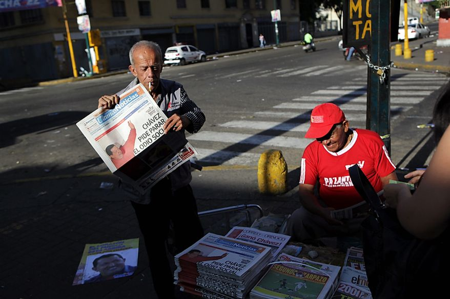 "A newspaper vendor holds a newspaper with a front-page headline that translates from Spanish as ""Chavez calls for an end to social hatred,"" in Caracas, Venezuela, on Monday, Oct. 8, 2012. Mr. Chavez won re-election and a new endorsement of his socialist project Sunday, surviving his closest race yet after a bitter campaign against opposition candidate Henrique Capriles. (AP Photo/Rodrigo Abd)"