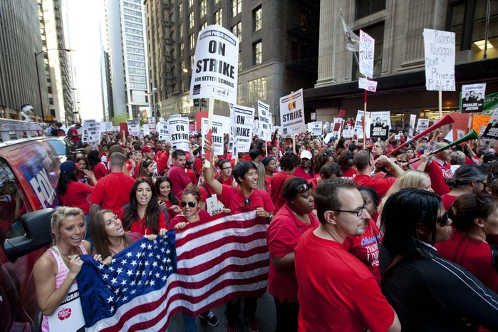 **FILE** Thousands of public school teachers rally Sept. 10, 2012, outside the Chicago Public Schools district headquarters on the first day of strike action over teachers' contracts in Chicago. (Associated Press)