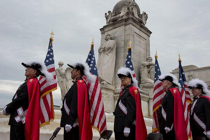Members of the Knights of Columbus hold American flags at the base of the National Columbus Memorial with its statue of Christopher Columbus during a ceremony honoring the memorial's 100th anniversary outside of Union Station in Washington, D.C. on Columbus Day, Monday, Oct. 8, 2012. (Barbara L. Salisbury/The Washington Times)