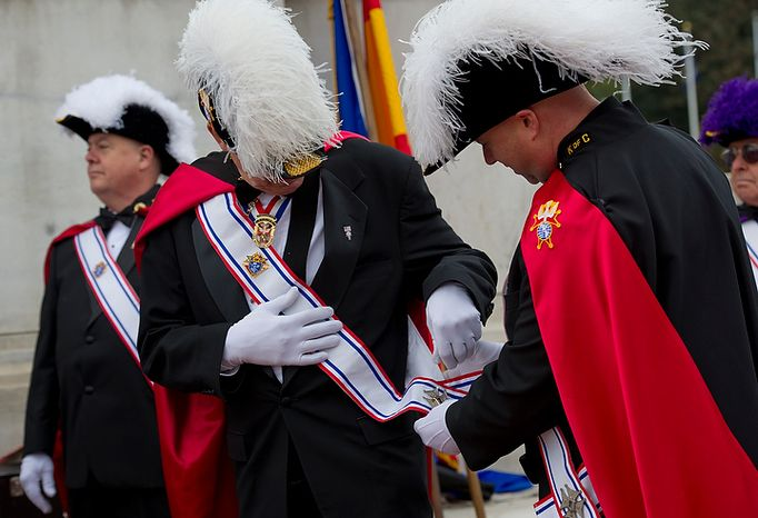 Joseph Pilkington, left, of Prince Frederick, Md., with the Knights of Columbus Lord Baltimore Assembly 2470, gets help adjusting his baldric from fellow assemblyman Tony Esser before the celebration of the 100th anniversary of the National Columbus Memorial outside of Union Station in Washington, D.C. on Columbus Day, Monday, Oct. 8, 2012. Knights of Columbus representatives from Washington, D.C., Maryland, Virginia and Pennsylvania all converged upon the memorial to help celebrate. (Barbara L. Salisbury/The Washington Times)