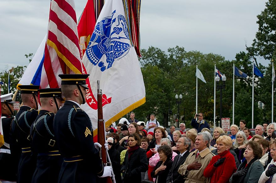 Audience members hold their hands over their hearts while saying the Pledge of Allegiance as the U.S. Marine Corps Honor Guard holds the flags during a celebration commemorating the 100th anniversary of the National Columbus Memorial outside of Union Station in Washington, D.C. on Columbus Day, Monday, Oct. 8, 2012. (Barbara L. Salisbury/The Washington Times)