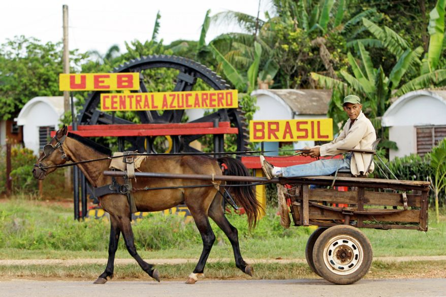 A man rides in a horse-drawn carriage outside the Brasil sugar processing plant in Jaronu, Cuba, on Sept. 8, 2012. (Associated Press)