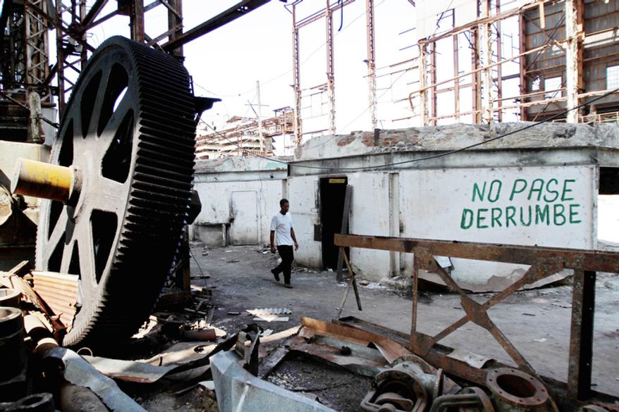 "A worker walks among old machinery at the Brasil sugar processing plant in Jaronu, Cuba. The words written on the wall read, in Spanish, ""Don't pass. Collapse."" The plant, launched in 1921, is getting a makeover and expected to be ready in time for the upcoming annual harvest and to start milling cane by February 2013. (Associated Press)"